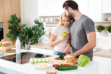 Foto de Picture of smiling young loving couple standing at kitchen and cooking together. Looking aside. - Imagen libre de derechos