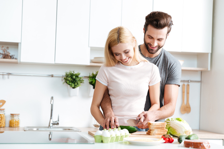 Foto de Beautiful smiling couple cooking together in a modern kitchen at home - Imagen libre de derechos