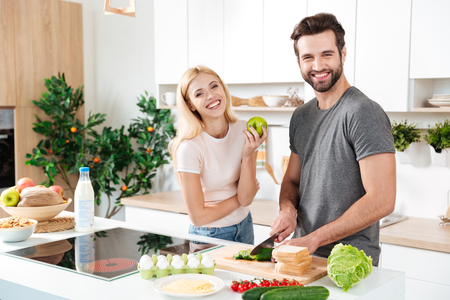 Photo pour Smiling couple spending time together in the kitchen at home - image libre de droit