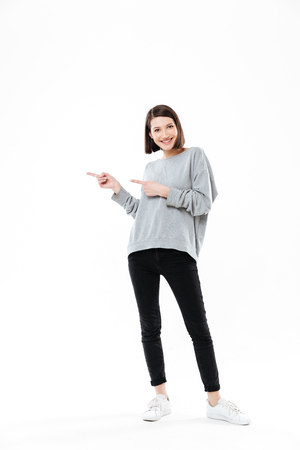 Photo pour Full length portrait of a casual woman pointing two fingers away at copy space isolated over white background - image libre de droit