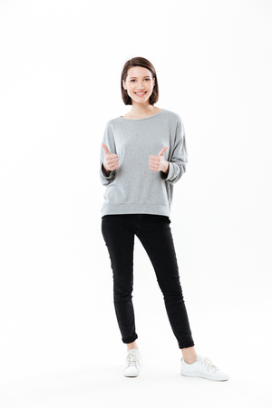 Foto de Full length portrait of a happy smiling girl standing and showing thumbs up gesture with two hands isolated over white background - Imagen libre de derechos