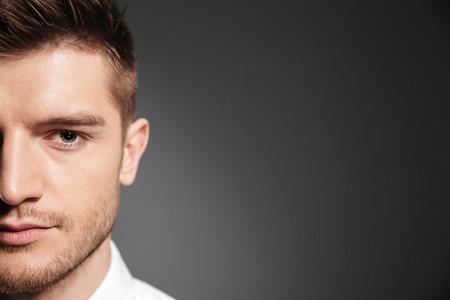 Foto de Half face portrait of a handsome confident man looking at camera isolated over grey background - Imagen libre de derechos