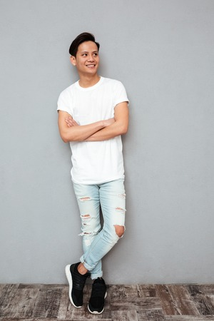 Photo for Photo of young smiling asian man standing with arms crossed over grey wall. Looking aside. - Royalty Free Image