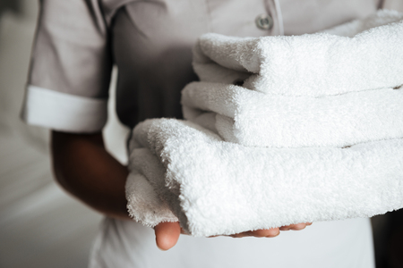 Photo pour Close up of a young hotel maid holding clean folded towels - image libre de droit