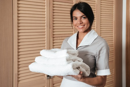 Photo pour Portrait of a smiling hotel maid holding fresh clean folded towels for the room - image libre de droit