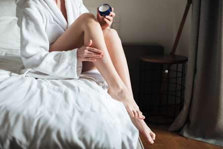 Photo pour Cropped image of a woman applying moisturizer cream on her leg in bedroom at home - image libre de droit