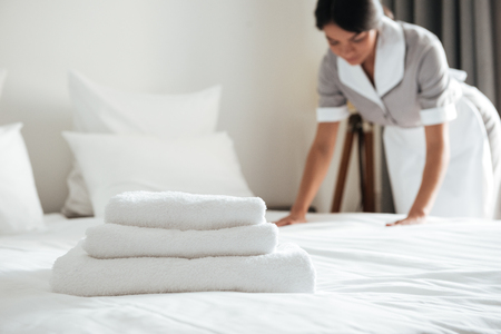 Photo pour Young hotel maid making the bed with clean fresh towels - image libre de droit