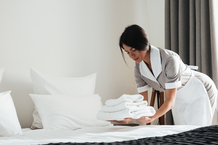 Photo for Young hotel maid putting stack of fresh white bath towels on the bed sheet - Royalty Free Image