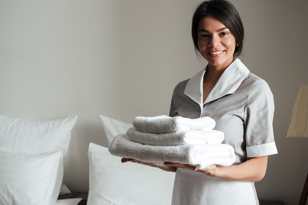 Photo for Portrait of a smiling hotel maid holding fresh clean folded towels for the room - Royalty Free Image
