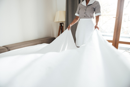 Photo pour Cropped image of a hotel maid changing the bed sheets - image libre de droit
