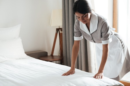 Foto de Young hotel maid setting up white bed sheet in hotel room - Imagen libre de derechos