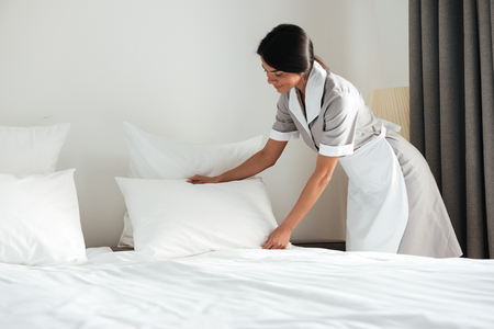 Photo pour Young hotel maid setting up white pillow on bed sheet in hotel room - image libre de droit
