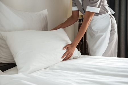 Photo for Cropped image of a female chambermaid making bed in hotel room - Royalty Free Image