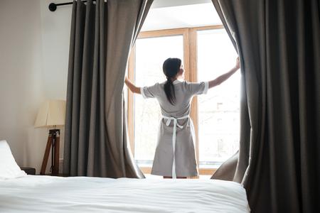 Foto de Female housekeeping chambermaid opening window curtains in the hotel room - Imagen libre de derechos