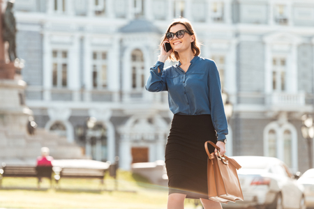 Photo pour Portrait of a cheerful young woman walking on a city street with mobile phone and bag - image libre de droit