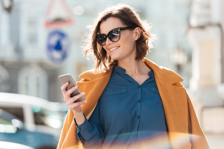Foto de Smiling casual woman in sunglasses looking at mobile phone while standing on a city street - Imagen libre de derechos