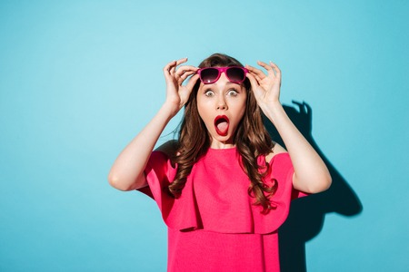 Photo for Portrait of a shocked young girl in dress looking at camera with her mouth open isolated over blue background - Royalty Free Image