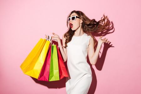 Foto für Photo of a pretty young brunette woman in white summer dress wearing sunglasses posing with shopping bags and looking aside over pink background. - Lizenzfreies Bild