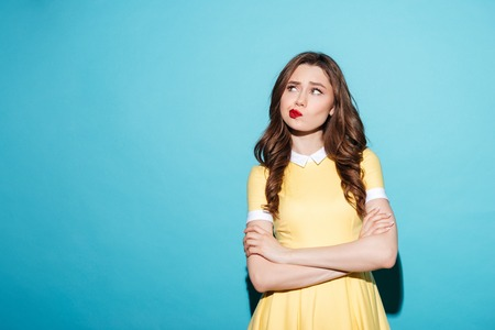 Photo pour Portrait of a disappointed cute girl in dress standing with arms folded and looking away isolated over blue background - image libre de droit