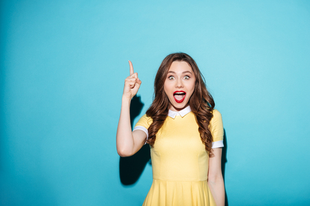 Photo pour Portrait of a beautiful excited girl in dress pointing finger up at copyspace isolated over blue background - image libre de droit