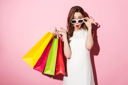 Photo pour Image of a shocked young brunette lady in white summer dress wearing sunglasses posing with shopping bags and looking at camera over pink background. - image libre de droit