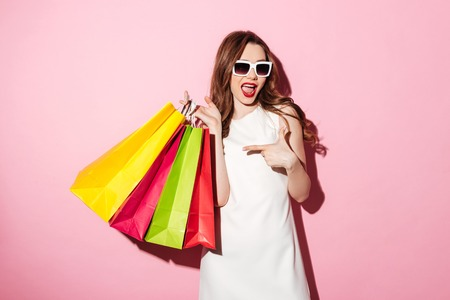 Photo pour Image of an amazing young brunette woman in white summer dress wearing sunglasses posing with shopping bags and looking at camera over pink background while pointing. - image libre de droit