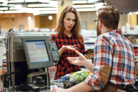 Photo pour Photo of confused young lady standing in supermarket shop near cashier's desk. Looking aside. - image libre de droit