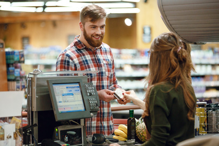 Photo for Photo of happy young man standing in supermarket shop near cashier's desk holding credit card. Looking aside. - Royalty Free Image