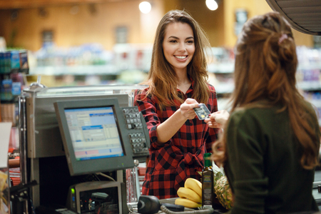 Photo pour Image of smiling young lady standing in supermarket shop near cashier's desk holding credit card. Looking aside. - image libre de droit