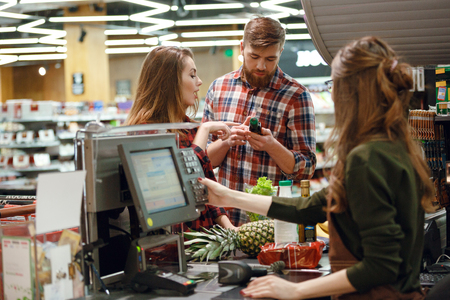 Photo for Photo of concentrated young couple standing in supermarket shop near cashier's desk. Looking aside. - Royalty Free Image