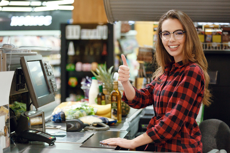 Photo pour Picture of cheerful cashier woman on workspace in supermarket shop. Looking at camera showing thumbs up. - image libre de droit