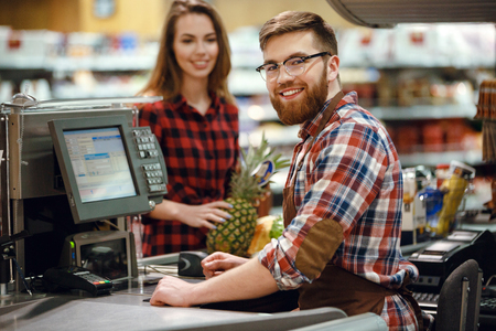 Photo for Image of cheerful cashier man on workspace in supermarket shop. Looking at camera. - Royalty Free Image