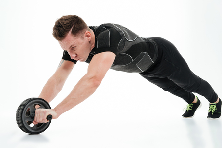 Photo for Full length portrait of a muscular healthy athlete man doing exercises with fitness roller equipment isolated over white background - Royalty Free Image
