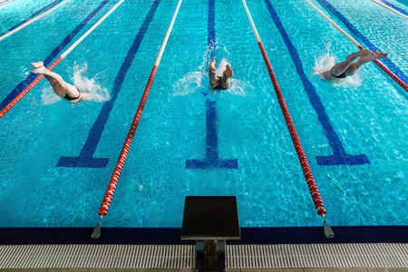 Foto de Rear view of three male swimmers diving into a swimming pool - Imagen libre de derechos