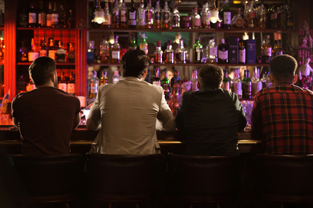 Foto de Back view of four young men drinking beer and talking while sitting at bar counter in a modern urban cafe - Imagen libre de derechos