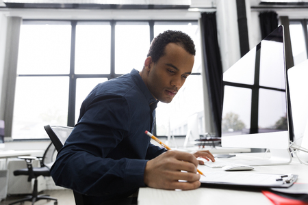 Photo for Afro american business man making notes while sitting at his desk - Royalty Free Image