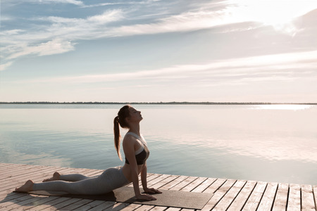 Photo for Photo of young sports lady at the beach make yoga exercises. - Royalty Free Image