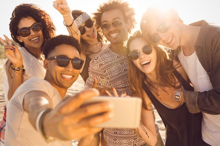 Foto de Group of multiracial happy friends taking selfie and having fun on a beach - Imagen libre de derechos