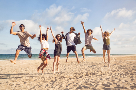 Photo for Portrait of excited young friends jumping on the beach - Royalty Free Image