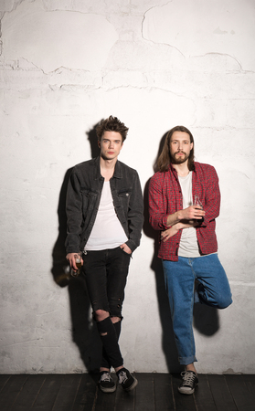 Foto de Picture of concentrated young hipsters friends standing over gray background drinking aerated sweet water. - Imagen libre de derechos