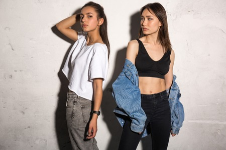Foto de Picture of concentrated young hipsters ladies standing over gray background. - Imagen libre de derechos