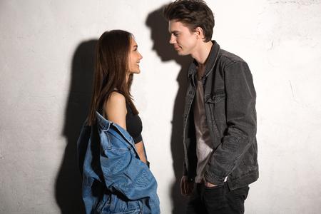 Foto de Image of smiling young hipster loving couple looking aside over gray background - Imagen libre de derechos