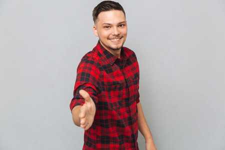 Photo for Smiling man in red shirt holds out his hand for a handshake and looking at the camera over gray background - Royalty Free Image