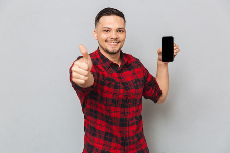 Foto de Portrait of a happy smiling casual man holding blank screen mobile phone and showing thumbs up gesture isolated on gray background - Imagen libre de derechos