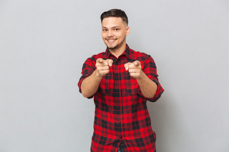 Photo for Smiling man in red shirt pointing at camera over gray background - Royalty Free Image