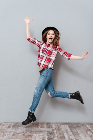 Photo pour Full length portrait of a carefree happy girl in plaid shirt celebrating success isolated over gray background - image libre de droit