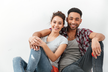 Photo pour Smiling beautiful multiethnic young couple sitting and hugging over white background - image libre de droit