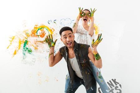 Foto de Happy young couple painting by hands and having fun over white background - Imagen libre de derechos