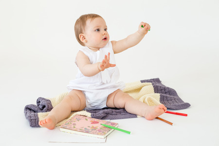 Photo pour Image of baby girl sitting on floor on plaid near markers and colouring isolated over white background. Looking aside. - image libre de droit