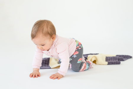 Photo pour Picture of pretty baby girl sitting on floor with plaid isolated over white background. Looking aside. - image libre de droit